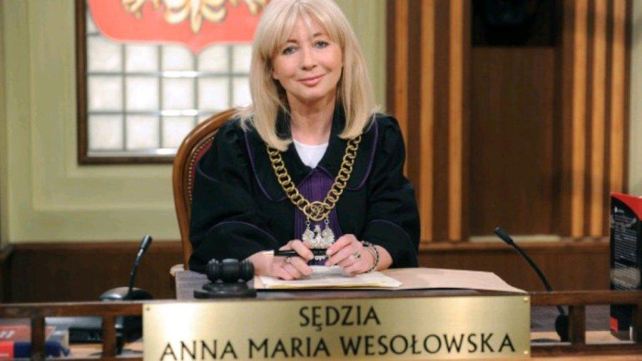 Grafika: Zdjęcie przedstawia sędzię Annę Marię Wesołowską w todze sędziowskiej, siedzącą przy ławie sędziowskiej. Przed sędzią znajduje się tabliczka z jej imionami i  nazwiskiem.