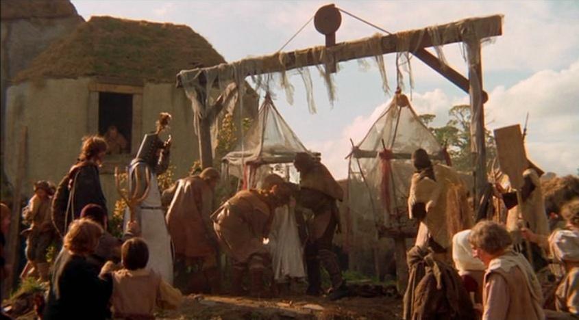 Grafika:Zdjęcie przedstawia scenę z filmu Monty Python i Święty Graal. Tłum średniowiecznych wieśniaków, wśród których stoi rycerz, patrzy jak czarownica sadowiona jest na wielkiej wadze.