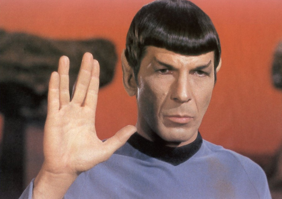 Grafika: Zdjęcie przedstawia Leonarda Nimoya w roli Spocka z serialu Star Trek. Spock trzyma uniesioną dłoń w geście salutu Wolkańskiego.