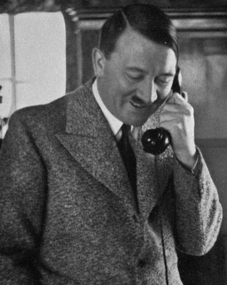 [Grafika: Zdjęcie przedstawia uśmiechniętego Adolfa Hitlera rozmawiającego przez telefon]