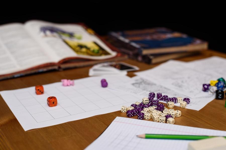 [Grafika: zdjęcie przedstawia leżące na stole przybory do gry fabularnej: wielościenne kości, karty postaci, ołówek, zeszyt a w tle karty i podręczniki mistrza gry]